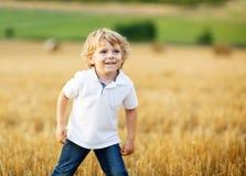 Rapaz pequeno de três anos que têm o divertimento no campo amarelo do feno Fotografia de Stock Royalty Free