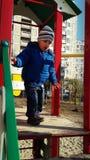 Rapaz pequeno deleitado pela altura das corrediças Foto de Stock Royalty Free