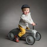 Rapaz pequeno doce que conduz um carro retro Imagens de Stock