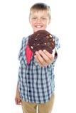 Rapaz pequeno doce que oferece lhe um bolinho do chocolate Imagens de Stock