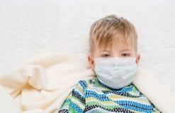 Rapaz pequeno doente na máscara dos cuidados médicos da medicina foto de stock royalty free