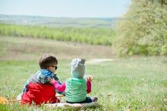 Rapaz pequeno e bebê que sentam-se em um fundo da paisagem verde imagem de stock