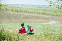 Rapaz pequeno e bebê que sentam-se em um fundo da paisagem verde imagem de stock royalty free