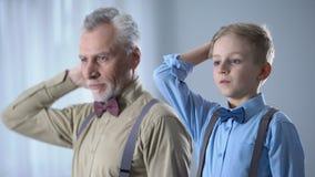 Rapaz pequeno e homem superior que ajustam o cabelo junto, semelhança de família, genética filme