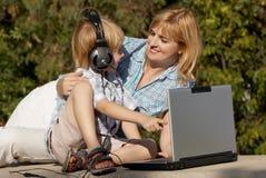 Rapaz pequeno e matriz com o portátil no parque fotografia de stock