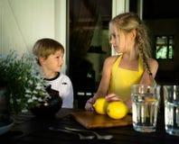 Rapaz pequeno e menina bonita em um vestido amarelo, limonada do limão Foto de Stock Royalty Free