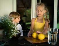 Rapaz pequeno e menina bonita em um vestido amarelo, limonada do limão Fotografia de Stock