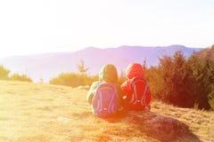 Rapaz pequeno e menina com as trouxas que têm o resto nas montanhas Imagens de Stock Royalty Free