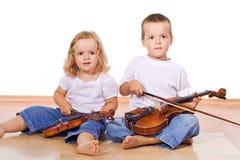 Rapaz pequeno e menina com violinos Imagem de Stock