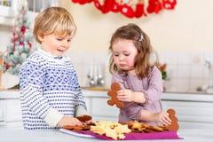 Rapaz pequeno e menina, irmãos, cookies de cozimento do pão-de-espécie na cozinha doméstica fotos de stock royalty free