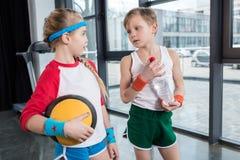 Rapaz pequeno e menina no sportswear que falam no estúdio da aptidão fotografia de stock royalty free