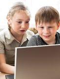 Rapaz pequeno e menina que aprendem o computador foto de stock royalty free