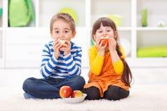 Rapaz pequeno e menina que comem maçãs fotos de stock