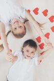 Rapaz pequeno e menina que encontram-se no assoalho Fotografia de Stock