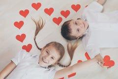 Rapaz pequeno e menina que encontram-se no assoalho Foto de Stock