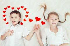 Rapaz pequeno e menina que encontram-se no assoalho Fotos de Stock Royalty Free