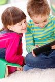 Rapaz pequeno e menina que jogam ou que leem da tabuleta fotografia de stock royalty free