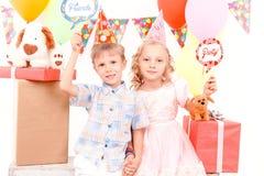 Rapaz pequeno e menina que levantam durante a festa de anos Imagem de Stock