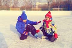 Rapaz pequeno e menina que patinam junto, esporte de inverno das crianças Imagens de Stock Royalty Free