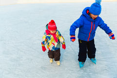 Rapaz pequeno e menina que patinam junto, esporte de inverno das crianças Imagem de Stock