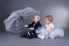 Rapaz pequeno e menina que sentam-se sob o guarda-chuva Imagem de Stock Royalty Free