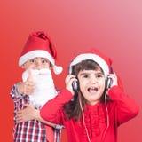 Rapaz pequeno e menina que vestem um chapéu de Santa foto de stock royalty free