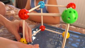 Rapaz pequeno e seu mum que jogam com grupo plástico colorido da construção Modelos da molécula 4K fecham-se acima do vídeo video estoque