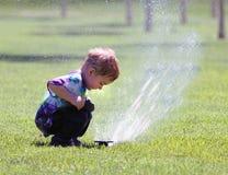 Rapaz pequeno e sistema de extinção de incêndios Imagem de Stock Royalty Free