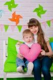 Rapaz pequeno e uma irmã mais idosa que sorri no banco Imagem de Stock Royalty Free