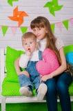 Rapaz pequeno e uma irmã mais idosa que sorri no banco Fotografia de Stock Royalty Free