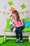 Rapaz pequeno e uma irmã mais idosa que sorri no banco Imagens de Stock Royalty Free