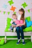 Rapaz pequeno e uma irmã mais idosa que sorri no banco Fotografia de Stock