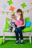 Rapaz pequeno e uma irmã mais idosa que sorri no banco Imagem de Stock