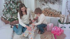 Rapaz pequeno e uma mãe nova que prepara presentes de Natal video estoque