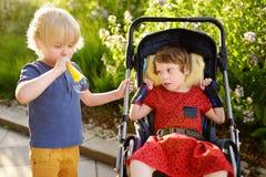Rapaz pequeno e uma menina deficiente que joga junto no parque do verão Paralisia cerebral da criança Família com criança deficie imagem de stock