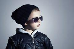 Rapaz pequeno elegante nos óculos de sol criança no tampão preto Estilo do inverno forma dos miúdos Imagens de Stock Royalty Free