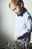 Rapaz pequeno elegante que joga a xadrez Miúdo esperto Criança pequena do gênio Jogo inteligente Placa de xadrez fotos de stock
