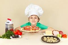 Rapaz pequeno em apetitoso do chapéu dos cozinheiros chefe lambido perto da pizza cozinhada Fotografia de Stock