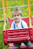 Rapaz pequeno em um balanço imagens de stock