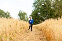 Rapaz pequeno em um campo de trigo imagens de stock