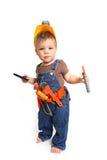 Rapaz pequeno em um capacete alaranjado com ferramentas e um telemóvel sobre Fotografia de Stock