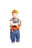 Rapaz pequeno em um capacete alaranjado e ferramentas em um fundo branco Foto de Stock