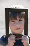 Rapaz pequeno em um frame fotografia de stock