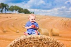 Rapaz pequeno em um pacote de feno Fotografia de Stock Royalty Free