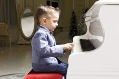 Rapaz pequeno em um terno que joga o piano Fotos de Stock Royalty Free