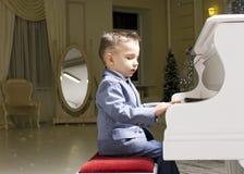Rapaz pequeno em um terno que joga o piano Fotos de Stock