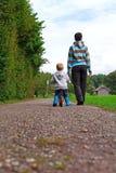 Rapaz pequeno em uma caminhada com sua mãe Rapaz pequeno em uma caminhada com sua mãe foto de stock