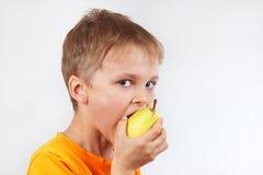 Rapaz pequeno em uma camisa alaranjada que come a pera amarela Fotografia de Stock