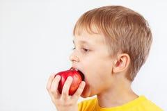 Rapaz pequeno em uma camisa amarela que come a maçã vermelha Imagem de Stock
