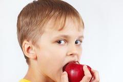 Rapaz pequeno em uma camisa amarela que come a maçã vermelha madura Imagem de Stock